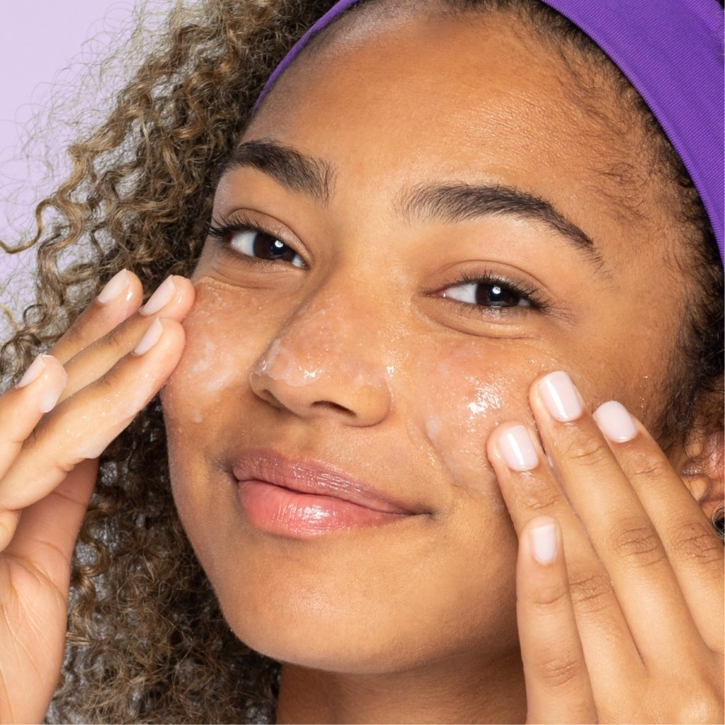 Young brown eye teen with purple headband and curls applying daily pore cleanser to cheeks