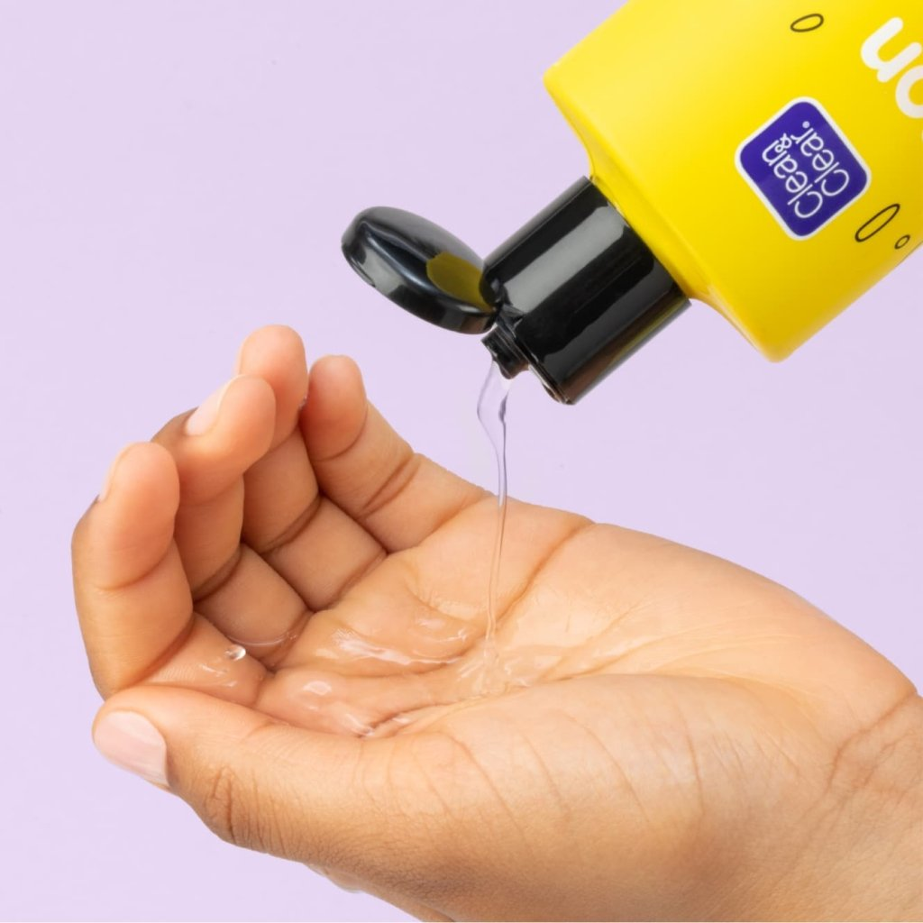 Clean & Clear lemon juice toner with yellow body and black cap being squeezed into palm of hand in front of light purple background