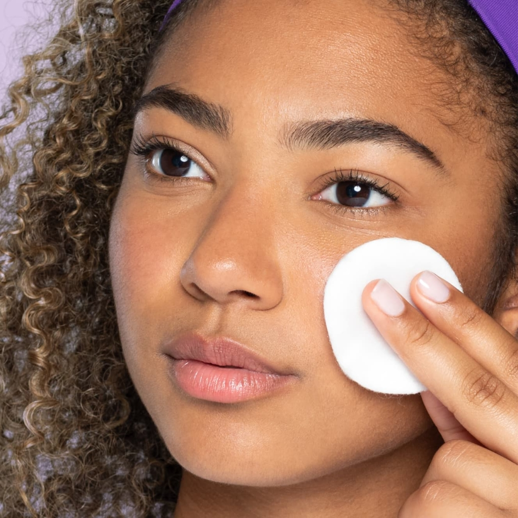 Young teen with brown eyes and curly brown hair with purple headband applies lemon juice toner with a white pad to cheek