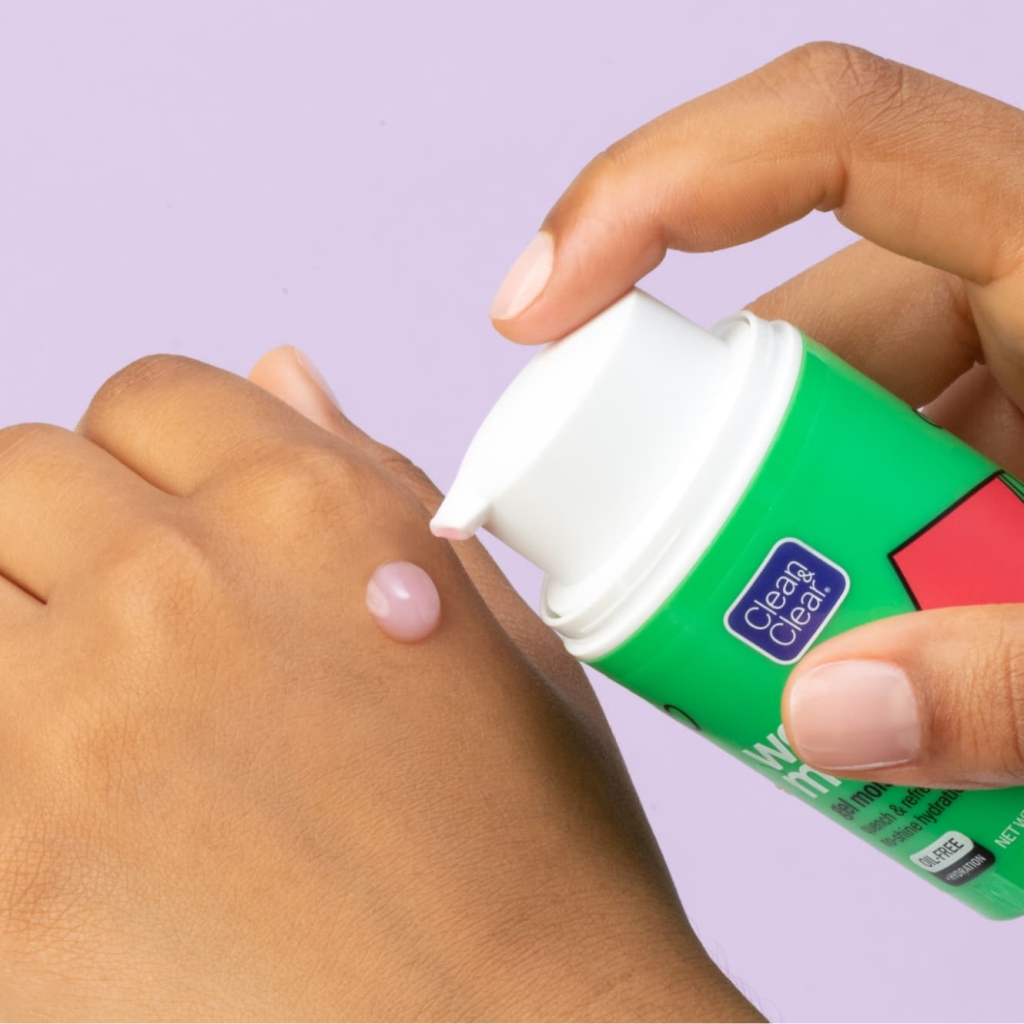 Drop of watermelon gel moisturizer is pumped from green bottle with white top onto back of fisted hand in front of light purple background