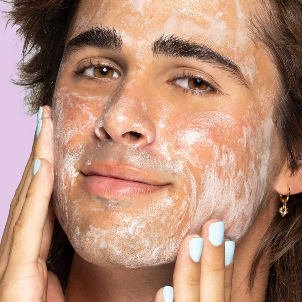 Teen rubbing in cleanser on soapy face