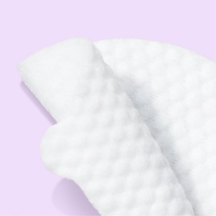 Close up of lemon exfoliating pad in front of light purple background